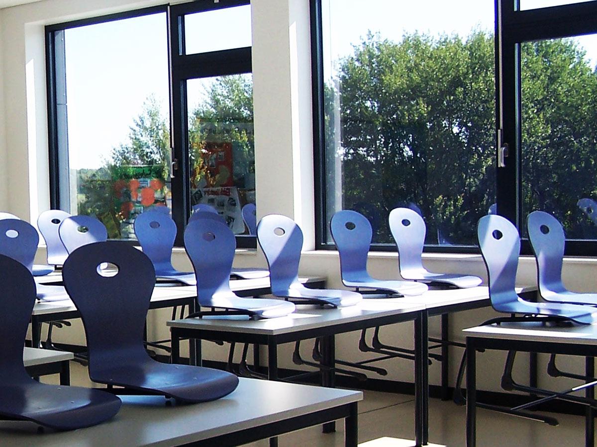 Klassenraum mit hochgestellten blauen Stühlen